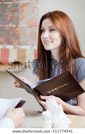 Woman keeps the menu choosing a dish to make an order - stock photo