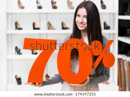 Woman keeps the model of 70% sale on shoes standing at the shopping center against the showcase with pumps - stock photo