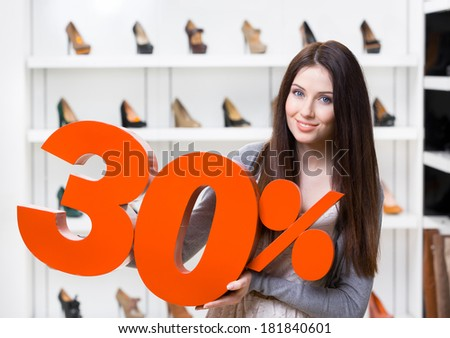Woman keeps the model of 30% sale on shoes standing at the shopping center against the showcase with pumps - stock photo