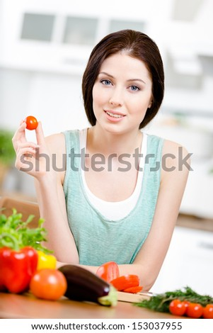 Woman keeps tomato sitting at the table with a great variety of vegetables for salad