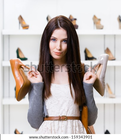 Woman keeps two heeled shoes in the shopping mall and can't choose the one for her - stock photo