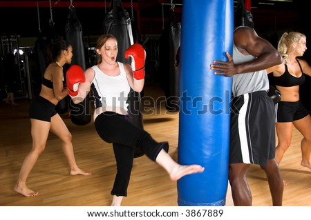 Woman kicking a heavy bag during a kick boxing class in an MMA gym - stock photo