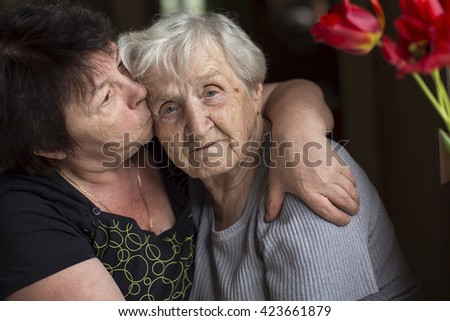 Woman kissing his old mother. Care for the elderly. - stock photo