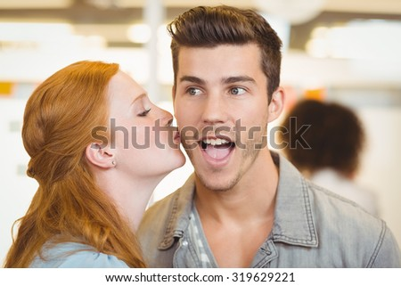 Woman kissing shocked businessman in creative office - stock photo