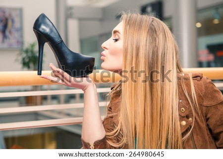 Woman kissing shoe. Women loves shoes concept. Blonde girl and black high heels shoes on the background of mall.  - stock photo