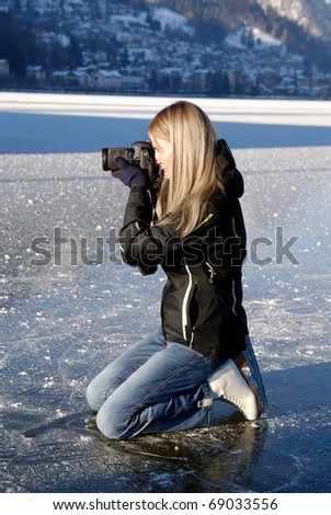 Woman kneeing on ice taking pictures on frozen lake - stock photo