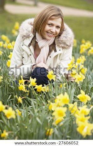 Woman Kneeling In Daffodils - stock photo
