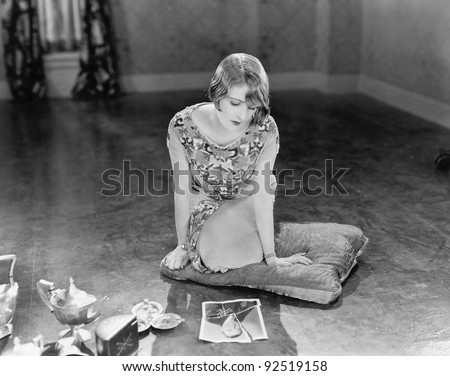 Woman kneeling on a pillow looking at a torn picture of a man - stock photo