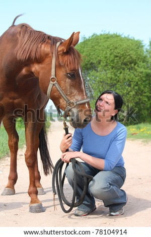 Woman kneeling on the ground and holding brown horse - stock photo