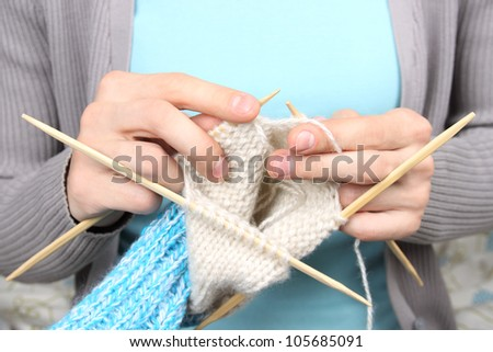 woman knitting blue socks closeup - stock photo