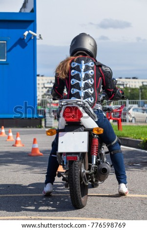 Woman L-driver is ready for driving slalom on training ground on motorbike, rear view