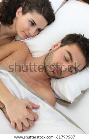 Woman laid near a sleeping man