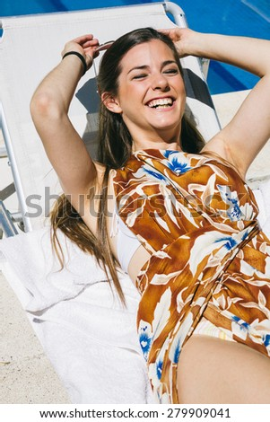 Woman laughing lying on a hammock - stock photo