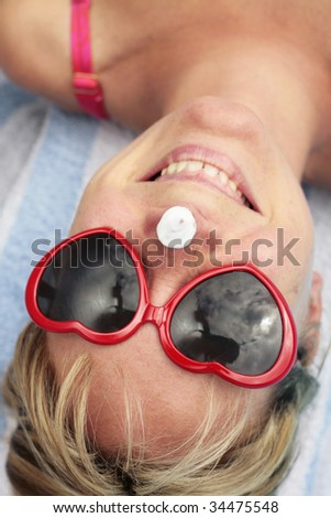 Woman laughing with sunscreen on her nose