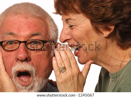 Woman laughs and whispers into husband's ear - stock photo