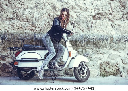 Woman launching a old scooter with pedal wearing casual clothes in urban background. - stock photo