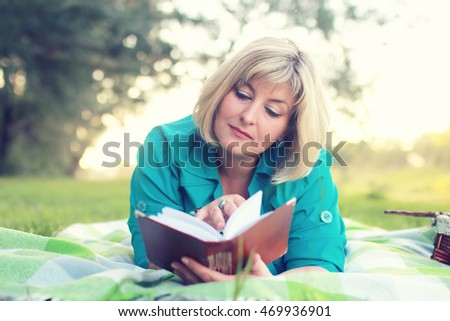woman lay and read book sun