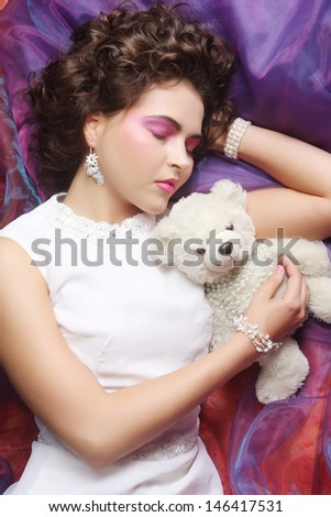 woman lay on organza with teddy bear - stock photo