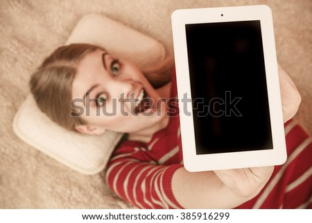 Woman laying and holding tablet computer with blank screen showing copyspace. Happy smiling woman advertising new modern technology. - stock photo