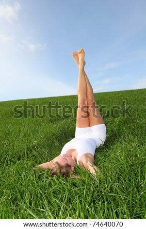 Woman laying down green field with legs up - stock photo
