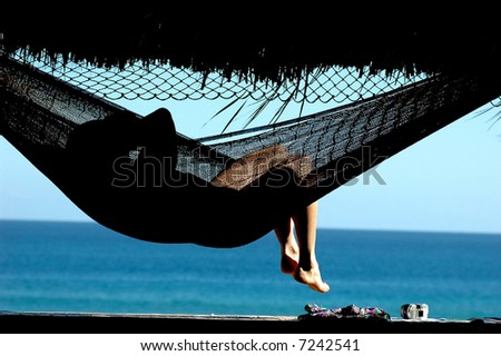 woman laying in hammock with view of ocean - stock photo