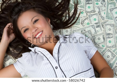 Woman laying in money - stock photo