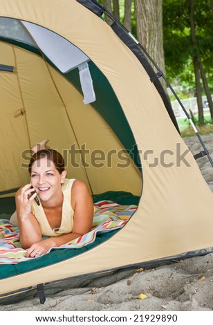Woman laying in tent using cell phone - stock photo