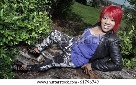 Woman laying on a tree in a nature setting - stock photo