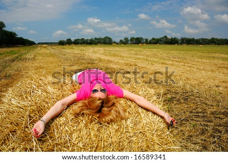Woman Laying on Bale of Hay - stock photo
