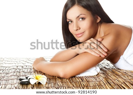 woman laying on bamboo mat in spa salon, looking at camera - stock photo