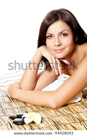 woman laying on bamboo mat in spa salon, looking at camera - stock photo