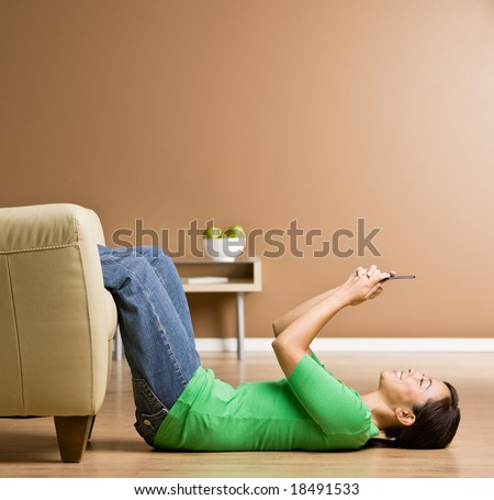 Woman laying on floor in livingroom text messaging on cell phone - stock photo