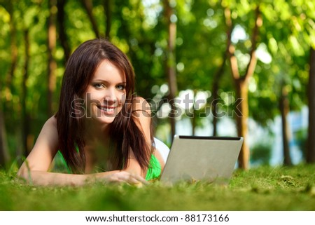 woman laying on grass with laptop in summer park - stock photo