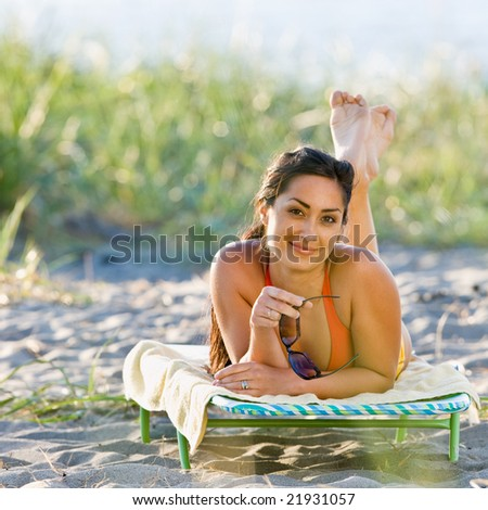 Woman laying on lounge chair at beach