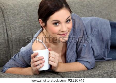 Woman laying on sofa with mug of coffee - stock photo