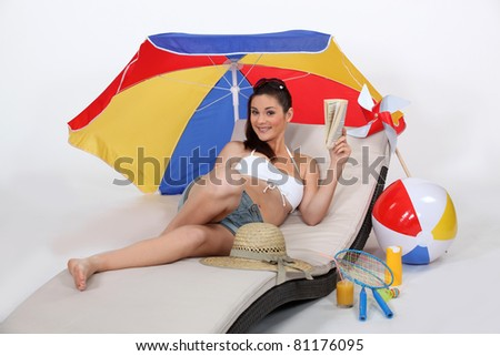 Woman laying on sun lounger - stock photo