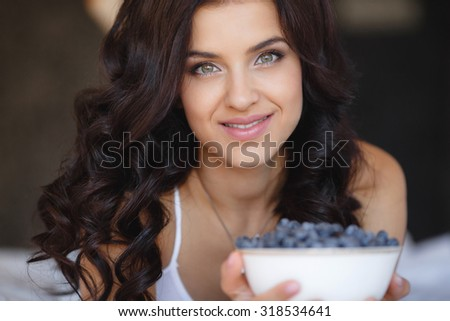 woman laying on the floor with bowl of berries blueberries at home. fresh morning. healthcare. Portrait of beautiful young woman eating a bowl of blueberries and smiling. Healthy food. - stock photo
