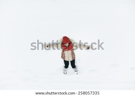 woman laying on the ground after a fresh snow fall  - stock photo