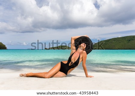 woman laying on tropical resort beach in elegant black swimwear and wide brim hat in caribbean exotic island sunbathing - stock photo