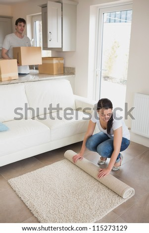 Woman laying out rug with man holding moving boxes in living room - stock photo