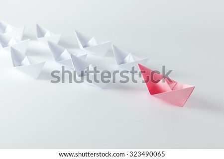 Woman leadership concept with pink paper ship leading among white - stock photo