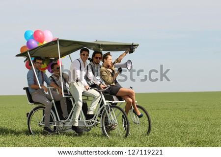 woman leading 4 guys on a bike - stock photo