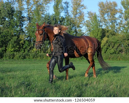 Woman leading her horse in evening pasture - stock photo