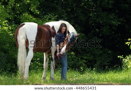 Woman leading horse on halter through the woods
