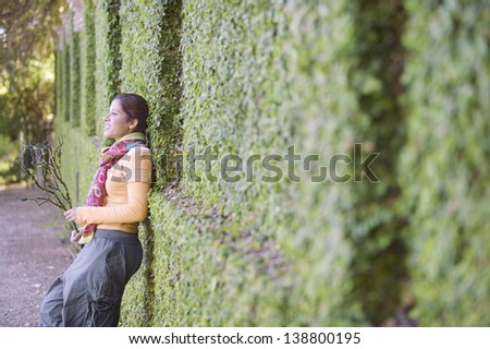 Woman leaning against a hedge