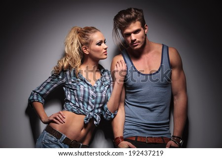 woman leaning against her boyfriend and looks at his while he looks at the camera - stock photo