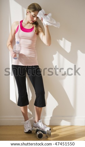 woman leaning against wall with towel and water after a workout - stock photo