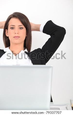 Woman leaning back from her laptop computer - stock photo