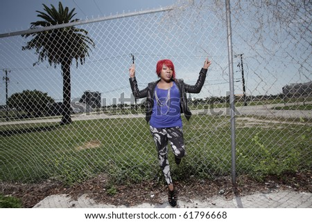 Woman leaning back on the fence - stock photo
