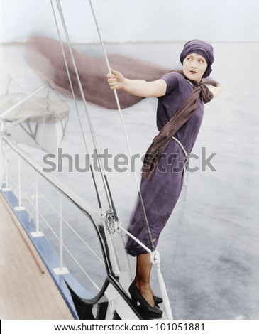 Woman leaning off boat into the wind - stock photo